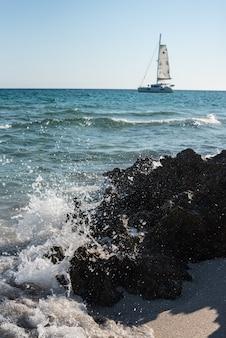 일부 바위와 배를 배경으로 해안에 부서지는 파도가 있는 바다.