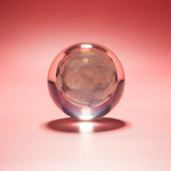 ピンクの背景にガラス玉の貝殻