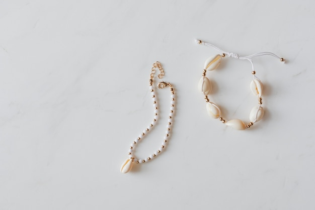 Seashell jewelries on white marble background