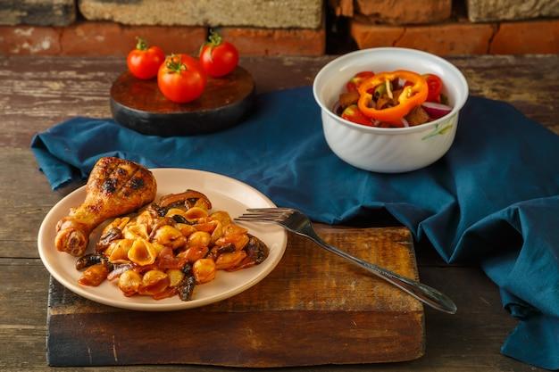 トマトの貝殻パスタと、フォークと野菜のサラダの横にある青いナプキンのグリルで焼いた鶏の脚。