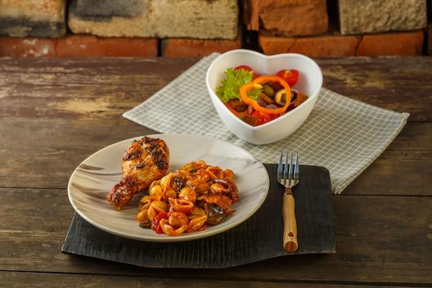 나무 테이블에 있는 스탠드에 그릴에 구운 닭 다리가 있는 토마토의 조개 파스타.