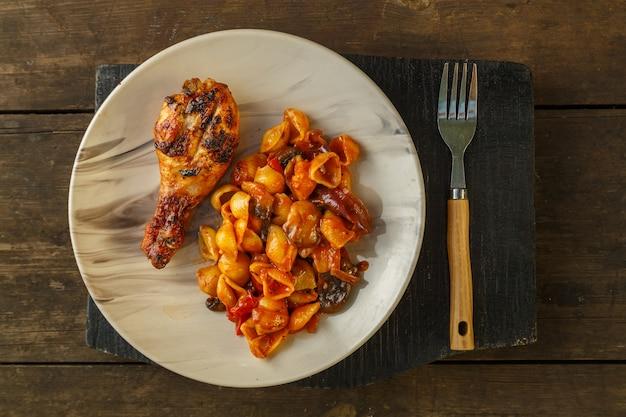 木製のグリルで焼いた鶏の脚とトマトの貝殻パスタ