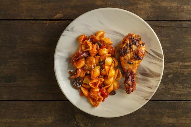 나무 테이블에 그릴에 구운 닭 다리가 있는 토마토의 조개 파스타 가로 사진