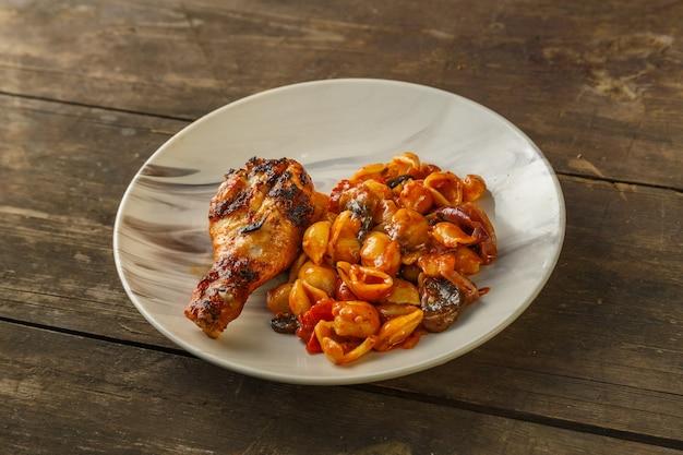나무 테이블에 그릴에 구운 닭 다리와 토마토의 조개 파스타.