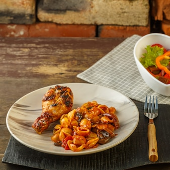 グリルチキンレッグと野菜サラダを添えたトマトの貝殻パスタ。正方形の写真