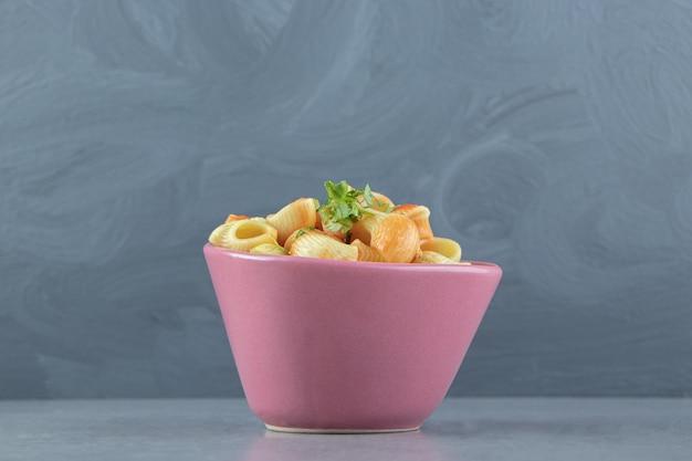 Паста из ракушек с соусом в розовой миске.