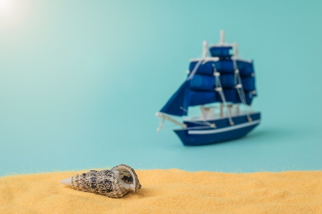 A seashell on the sand against a sailboat on a blue surface. the concept of travel and adventure.