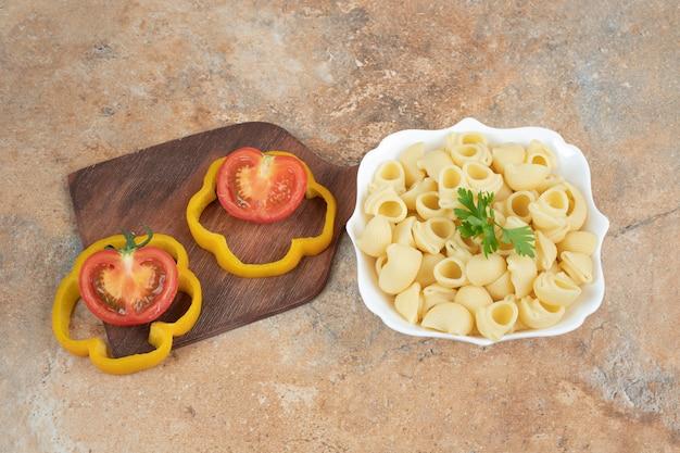 고추와 토마토 조각 그릇에 조개 모양의 파스타