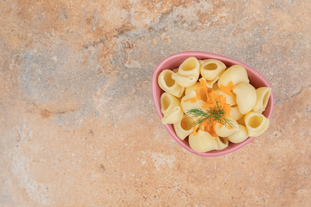 Паста в форме ракушки с ломтиками моркови и укропом в миске.