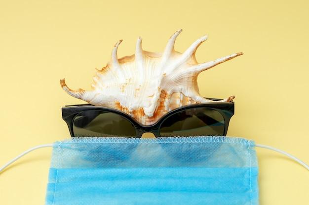 Морская ракушка с очками и медицинской маской.