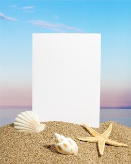 모래 해변에 빈 카드와 조개와 불가사리