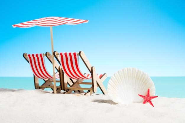 해변에서 우산 아래 조개와 두 개의 선베드
