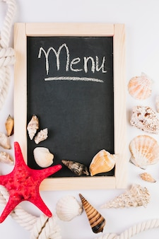 Seashells aroundblackboard with menu writing