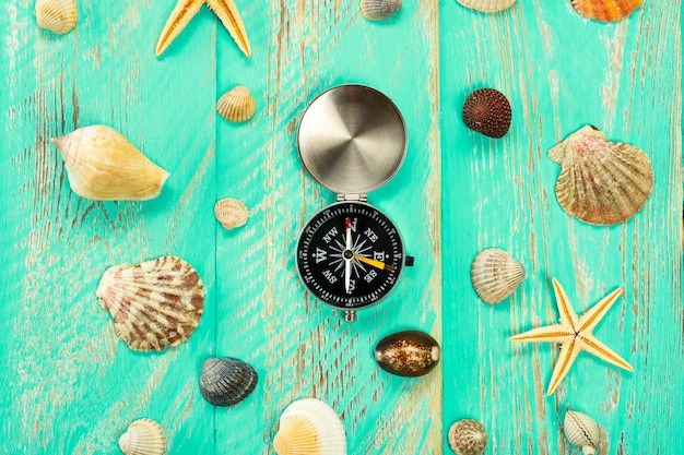 Seashells and compass on blue wooden table background