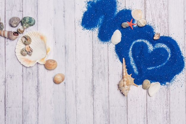Seashells decoration blue sand wooden background scenery ocean. high quality photo