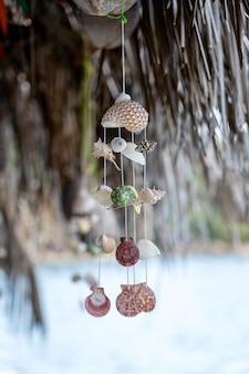 タイの熱帯のビーチでロープにぶら下がっている貝殻、クローズアップ