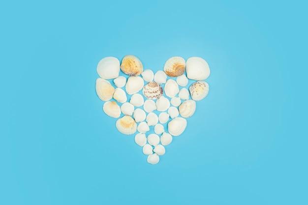 貝殻から作られた色付きの背景のハートの形の貝殻高品質の写真