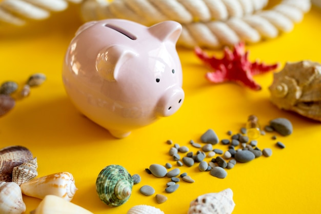 Seashells, pebbles and piggy bank on a yellow background.