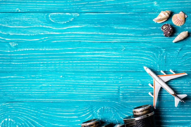 Seashells, plane and on blue wooden background