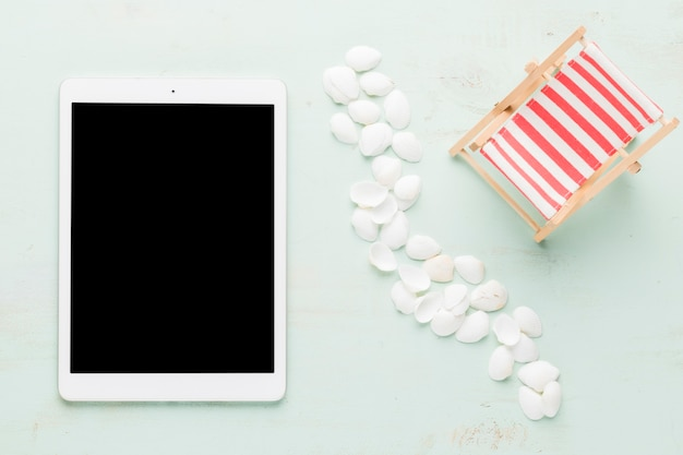 Seashells and tablet on light surface