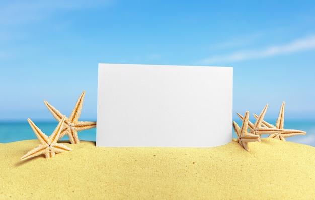 Seashells with blank card on sand beach
