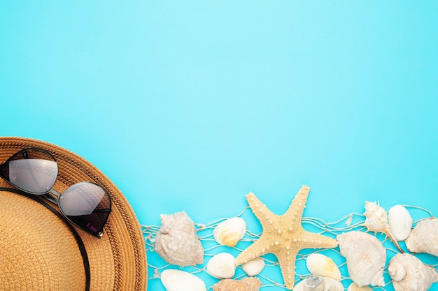 Seashells with hat on blue background. top view