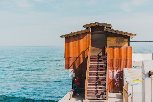 Seashore dock and brown wooden house with staircase on sea water. stairway to building. ocean view. horizon. tower for ships and blue. blue water. sky. stairs