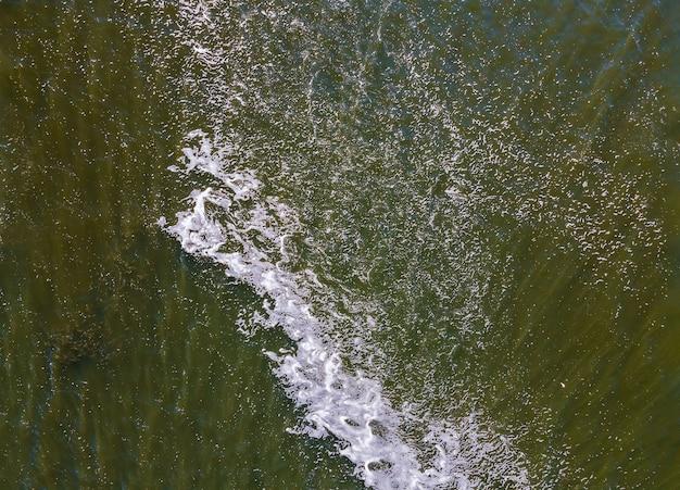 Берег моря с катящимися волнами, вид с высоты