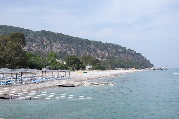 風景のあるサンラウンジャーのある海辺のビーチ。七面鳥。山と海