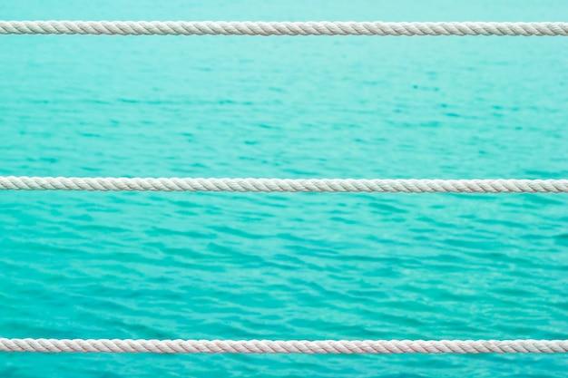 日光の下で海辺の柵ロープの白い色。