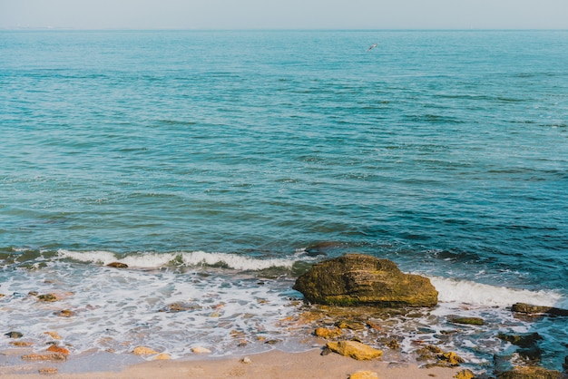 Seaside sand beach with big stones. ocean view to horizon. wavy water in ocean. nature. power. rocky bay. waterfront. peaceful view on a sea. summer trip. relaxation view. turquoise color