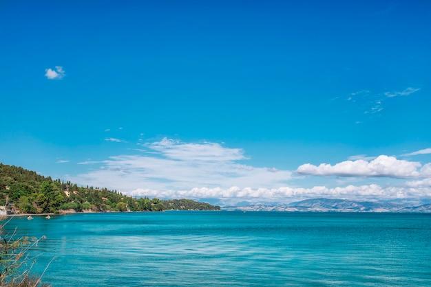 코르푸 섬, 그리스에 보트와 해변. 관광객을위한 나무와 호텔, 부두를 걷는 사람들이있는 이오니아 바다 해변의 아름다운 풍경.