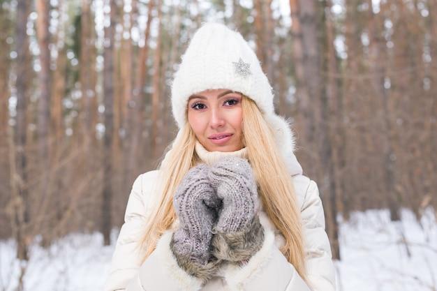 季節と人々のコンセプト-白衣と白い帽子に身を包んだ魅力的な金髪の女性が立っている