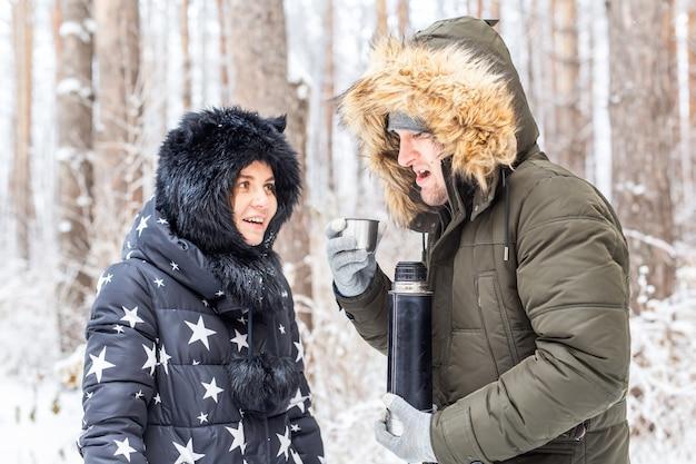 Концепция сезона и прогулки счастливая пара пьет горячий чай в зимнем лесу