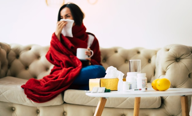 A season flu. close-up of a coughing girl, suffering from illness at home, drinking tea, covered with a red blanket.