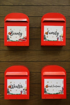 Season greetings new year wishes on four red post boxes hanging on wooden wall