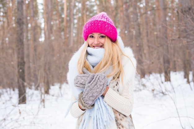 Season and people concept - attractive blond woman dressed in white coat and pink hat standing in a forest