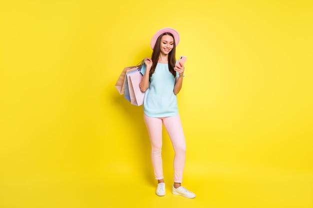 Сезонная распродажа, концепция уведомления торгового центра, фото всего тела, девушка, использование смартфона, чтение новостей, проведение, много сумок, одежда, розовая, синяя футболка, кепка, солнечная шляпа, штаны, изолированные, яркий, блеск, цвет фона