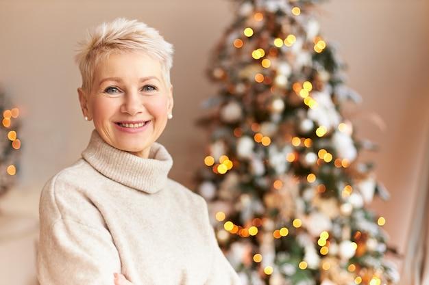 季節、冬、休日、お祝いのコンセプト。自宅で飾られた松の木でポーズをとって、クリスマスの準備を楽しんでいる短い髪と広い輝く笑顔を持つ陽気な中年の女性の写真