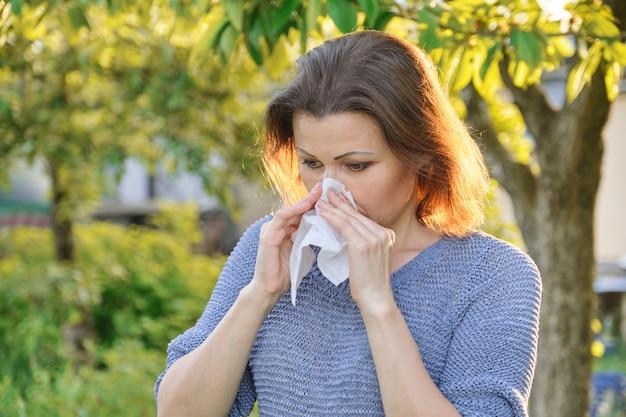 Сезонная аллергия, женщина с носовым вытиранием, чихание, вытирая нос на открытом воздухе