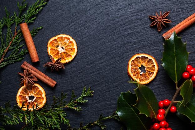 Концепция сезонного фона зимние или рождественские специи и рождественские листья и ягоды падуба на черной шиферной каменной доске с копией пространства