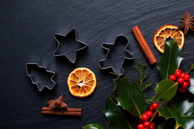季節の背景の概念冬またはクリスマスのスパイス、クッキーカッター、コピースペースのある黒いスレート石のボード上のクリスマスのヒイラギの葉とベリー