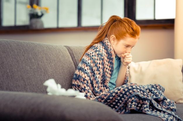 Seasonal cold. unhappy red haired girl coughing into her hand while suffering from cold