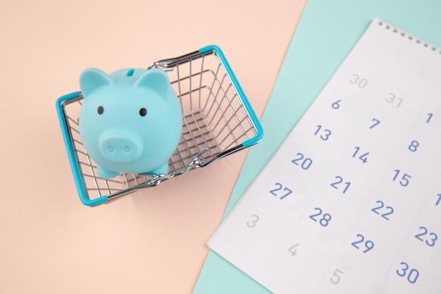 季節割引。カレンダー、カラフルな背景の上のスーパーマーケットのバスケットと青い貯金箱。