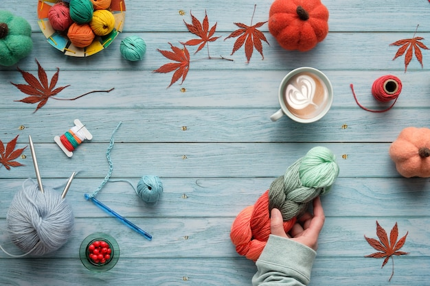 Seasonal fall flat lay on faded light blue wood boards. top view of the wooden table with yarn balls, decorative felt pumpkins