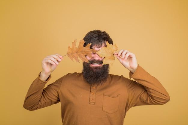 Сезонная мода осенняя одежда улыбающийся человек закрыл глаза осенним листом осеннее настроение осеннее время
