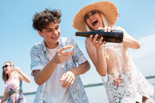 日当たりの良いビーチでの休息を祝う友人のビーチリゾートグループでの季節のごちそう