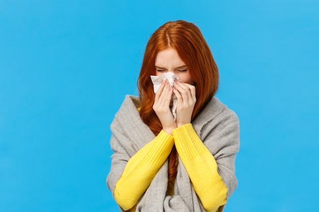 季節性インフルエンザ。かわいい赤毛の女子学生が風邪をひいた、ナプキンでくしゃみをし、セーターを着ている