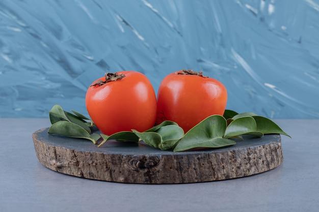 季節の果物。木の板に柿