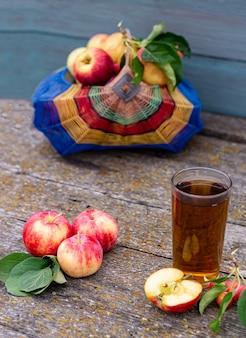 木製の背景の垂直写真のガラスのバスケットとリンゴジュースの季節の収穫